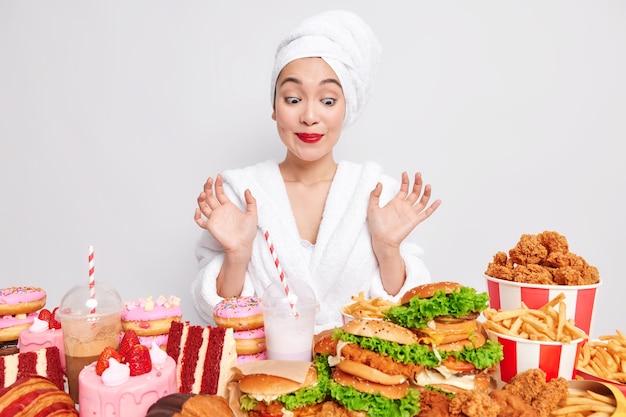 Głodna młoda azjatka patrzy z pokusą na różne fast foody
