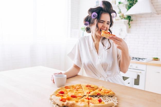 Głodna młoda gospodyni domowa siedzi w kuchni i je pizzę. ugryź kawałek jedzenia. sam w pokoju. gospodyni cieszy się życiem bez pracy. trzymaj kubek w rękach.