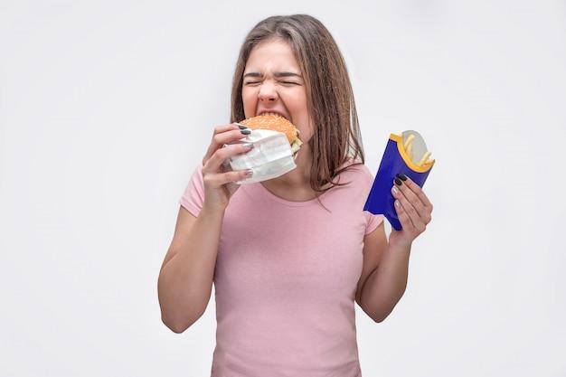 Głodna młoda kobieta ugryzła kawałek burgera