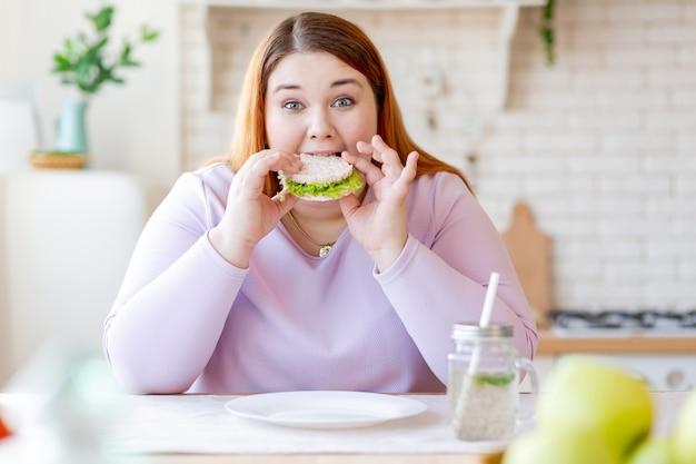 Głodna pulchna kobieta patrzy na ciebie podczas gryzienia smacznej kanapki