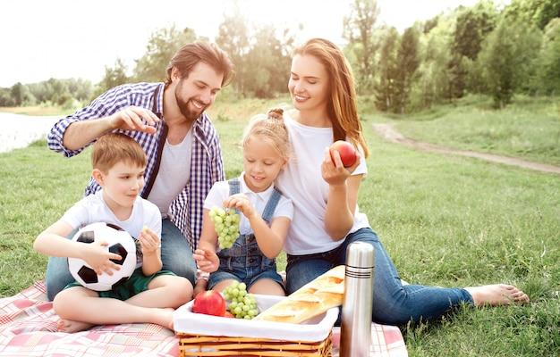 Głodna rodzina siedzi na kocu i patrzy na kosz z jedzeniem. kobieta ma jabłko w dłoniach. dziewczyna trzyma w rękach winogrona. chłopiec je kawałek winogron. człowiek chce złapać jedzenie z kosza