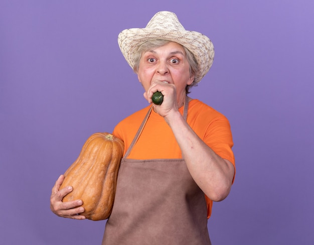 Głodna starsza kobieta ogrodniczka w kapeluszu ogrodniczym trzymająca dynię i gryzącą ogórek