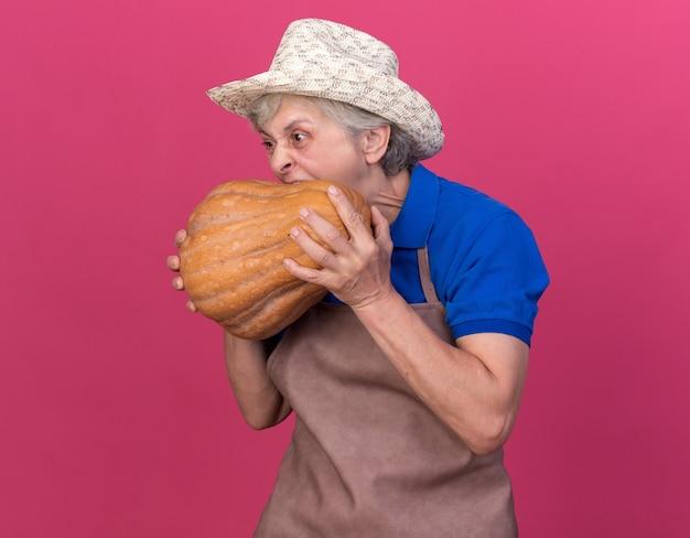 Głodna starsza kobieta ogrodniczka w kapeluszu ogrodniczym, trzymająca się i udając, że gryzie dynię