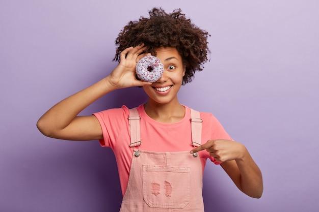Głodna uśmiechnięta dziewczyna zakrywa jedno oko słodkim glazurowanym pączkiem, ma niezdrowe odżywianie, wskazuje na różowy kombinezon, przerywa dietę