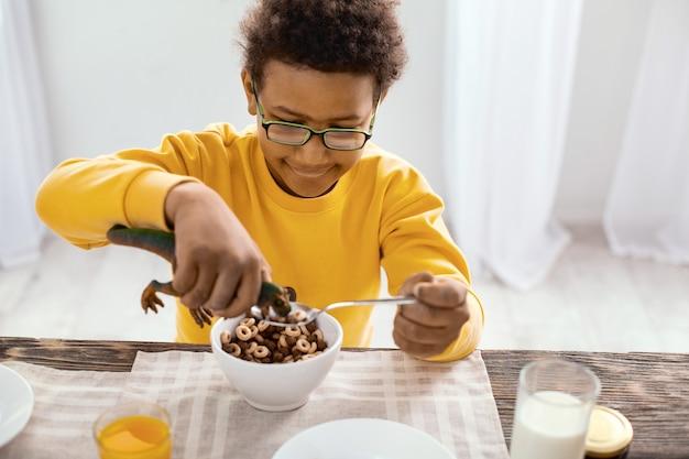 Głodna zabawka. radosny chłopiec w wieku przedszkolnym siedzący przy stole i jedzący śniadanie karmiącego zbożem zabawkowego dinozaura