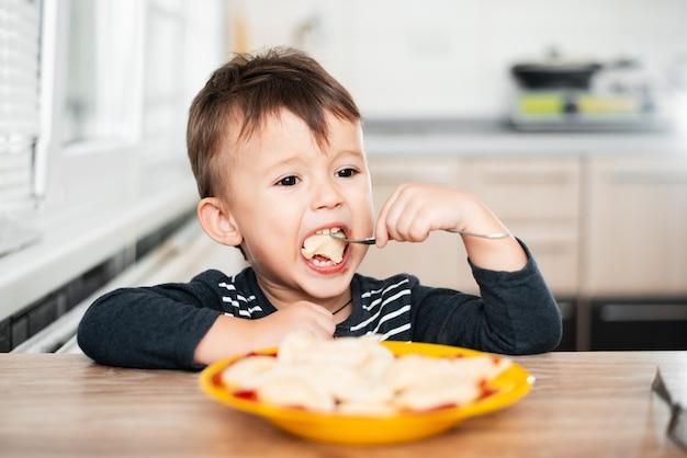 Głodne dziecko je pierogi w kuchni, siedząc przy stole w szarej kurtce