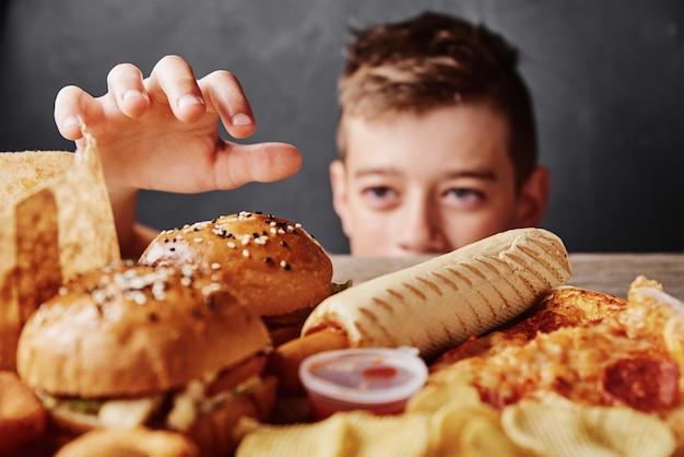 Głodny chłopiec patrzy na smaczne jedzenie i bierze hamburgera ze stołu