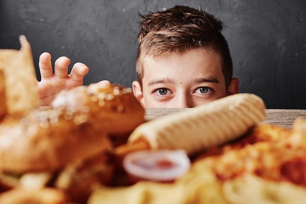 Głodny chłopiec patrzy na smaczne jedzenie i bierze hamburgera ze stołu.