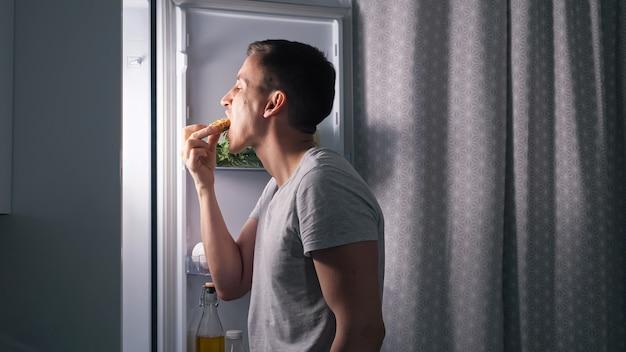 Głodny mąż je pyszne ciasto stojąc w ciemnej kuchni