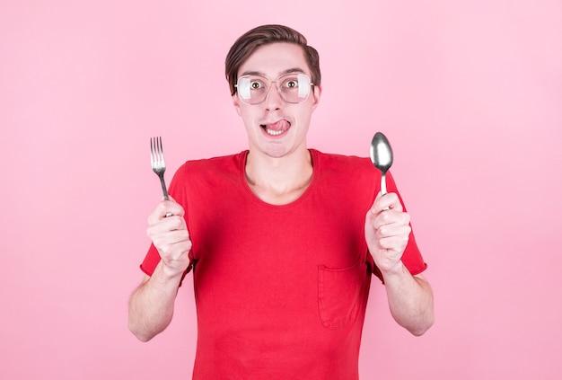 Głodny mężczyzna trzyma w rękach widelec i łyżkę i myśli o pysznym jedzeniu na różowym tle