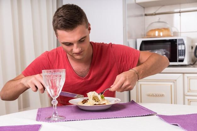 Głodny młody człowiek je makaron siedząc przy stole w małej kuchni w domu