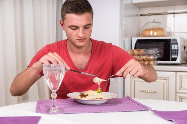 Głodny młody człowiek układa makaron spaghetti na widelec siedząc przy stole w domowej kuchni w porze kolacji