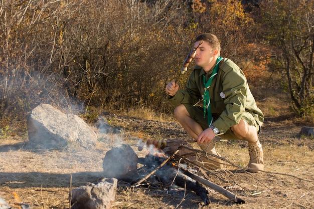 Głodny młody harcerz gotuje kiełbaski nad małym otwartym ogniem na polanie, gdy bada dziką przyrodę