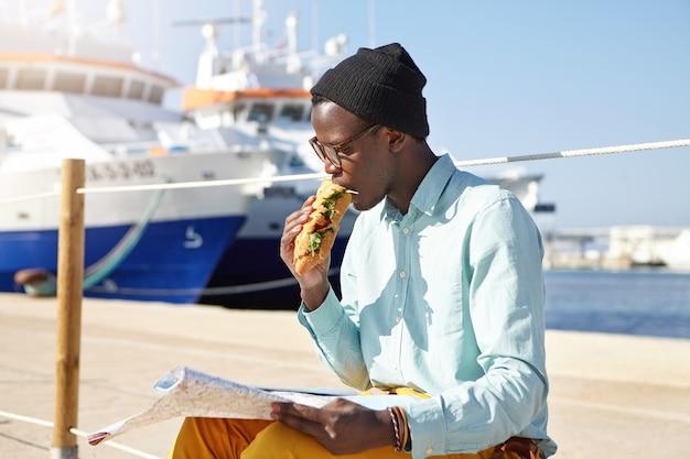 Głodny turysta mężczyzna w modnych ubraniach i dodatkach jedzący kanapkę