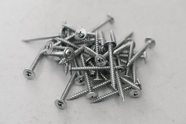 Głodzony z metalu leżącego luźno w stosie na jasnoszarym tle. łączniki do konstrukcji