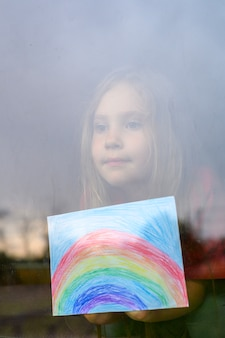 Głośny efekt. siedmioletnia dziewczynka z rysunkową tęczą patrzy przez okno podczas kwarantanny covid-19. zostań w domu, bądźmy zdrowi. obraz pionowy