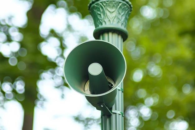 Głośny głośnik zewnętrzny. system dźwiękowy w publicznym parku. głośnik do syreny, alarmu lub ogłoszenia. vintage zielony głos mówi przez megafon na filarze do transmisji informacji, allert
