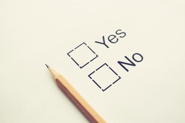 Głosuj na wybór tak lub nie - pole wyboru na białym papierze z ołówkiem. stonowanych koncepcja listy kontrolnej
