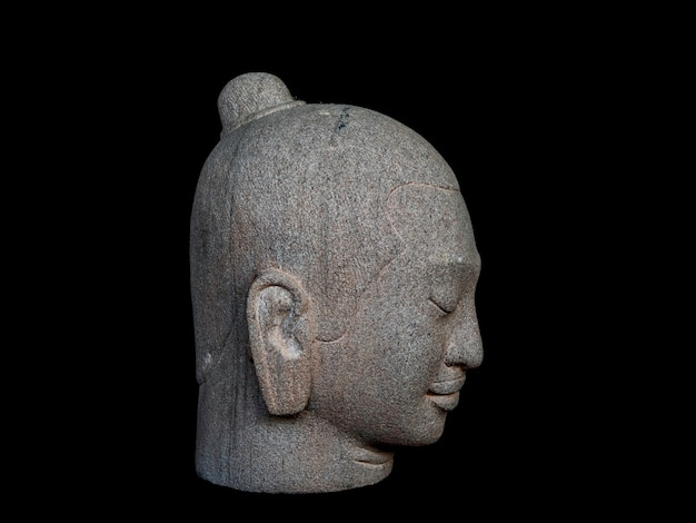 Głowa buddy wyrzeźbiona z kamienia na białym tle na ciemnym tle. twarz antycznego kamienia buddy, widok z boku.