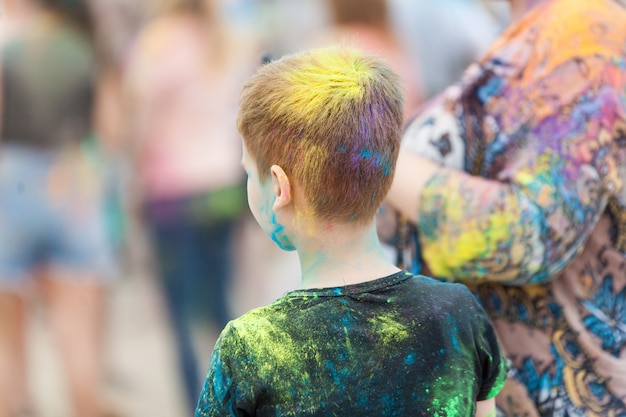 Głowa chłopca z kolorowymi włosami na festiwalu holi