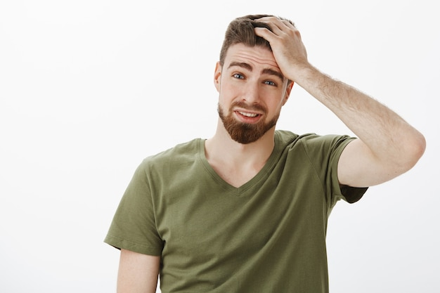 Głowa faceta boli podczas myślenia, czuje się przygnębiony i zdenerwowany, winny nie wymyślania dobrych pomysłów, trzymając rękę na włosach, marszcząc brwi i mrużąc oczy, będąc niezadowolonym i ponurym, przepraszając za białą ścianę
