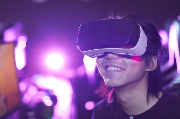 Głowa i ramiona portret młodego azjatyckiego mężczyzny noszącego zestaw vr podczas grania w gry wideo i radośnie uśmiechnięty, kopia przestrzeń