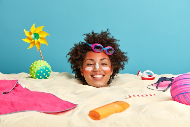 Głowa młodej kobiety z kremem przeciwsłonecznym na twarzy otoczonej akcesoriami plażowymi