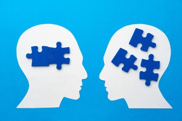 Głowa papercut z kawałkami puzzli na niebieskiej powierzchni