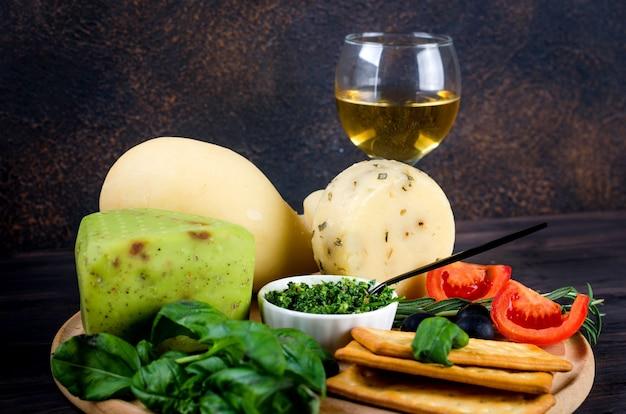 Głowa sera domowej roboty z bazylią pesto na starej ciemnej desce i kieliszkiem wina na stole. świeży produkt mleczny, zdrowa żywność ekologiczna. pyszna przystawka.