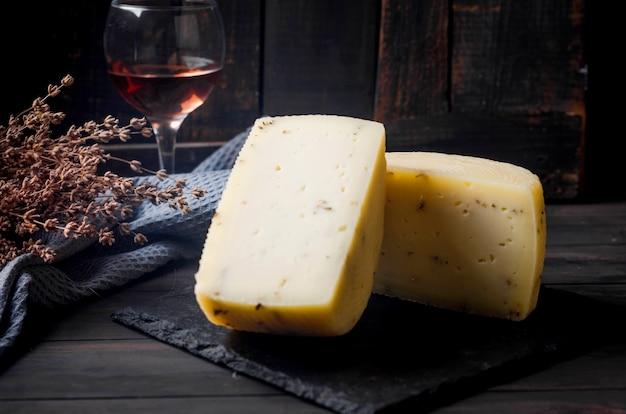 Głowa sera domowej roboty z lawendą na starej ciemnej drewnianej desce i kieliszek wina na stole. świeży produkt mleczny, zdrowa żywność ekologiczna. pyszna przystawka.