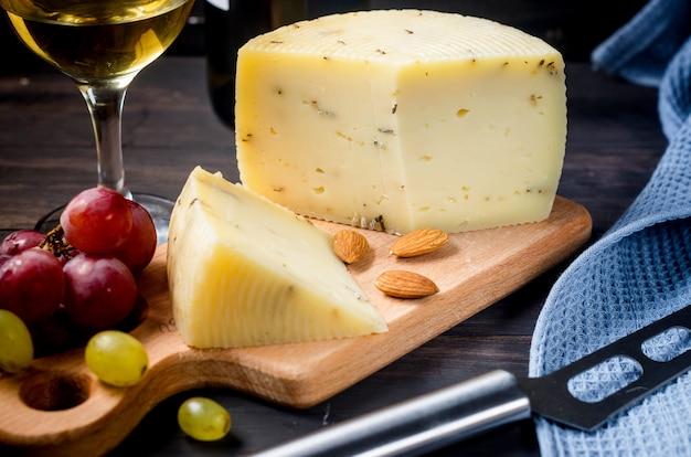 Głowa sera domowej roboty z lawendą na starej ciemnej drewnianej desce i kieliszek wina na stole.
