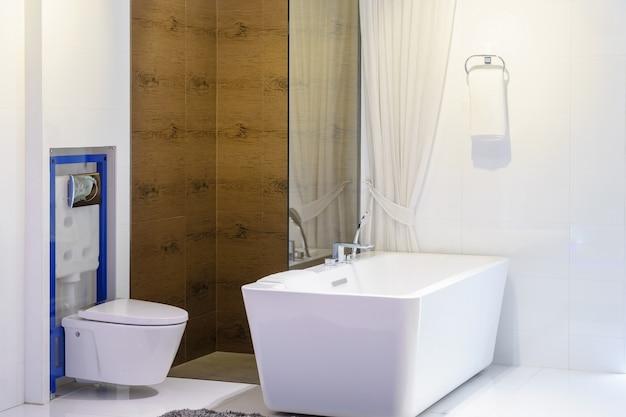 Główna łazienka w nowym luksusowym domu: wanna i prysznic z drzwiami prysznicowymi z płytek i szkła