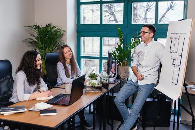 Główny inżynier mówi o nowym kreatywnym pomyśle w planach budynku, podczas gdy dwie współpracownicy zauważają w notatniku w nowoczesnym biurze.