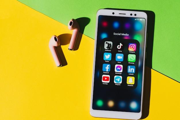 Główny popularny klub, tik tok, instagram, facebook, whatsapp, snapchat, youtube, twitter i na ekranie smartfona ze słuchawkami.