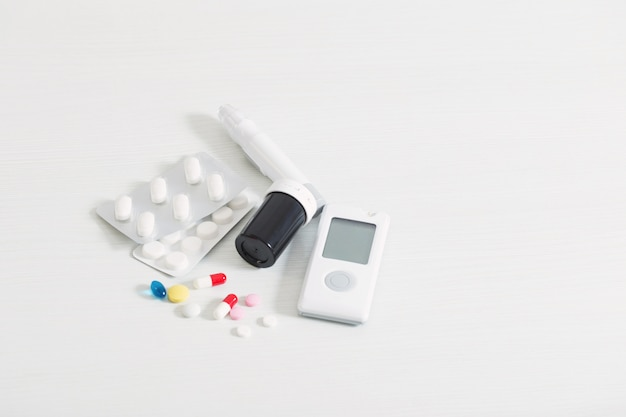 Glukometr i pigułki na białym drewnianym stole