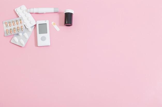 Glukometr i pigułki na różowym stole