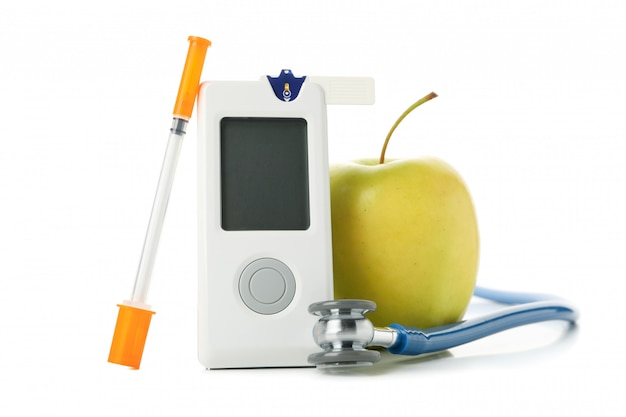 Glukometr, strzykawka i jabłko na białym tle