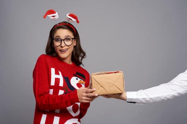 Głupek kobieta z prezentem bożonarodzeniowym i śmieszną twarzą