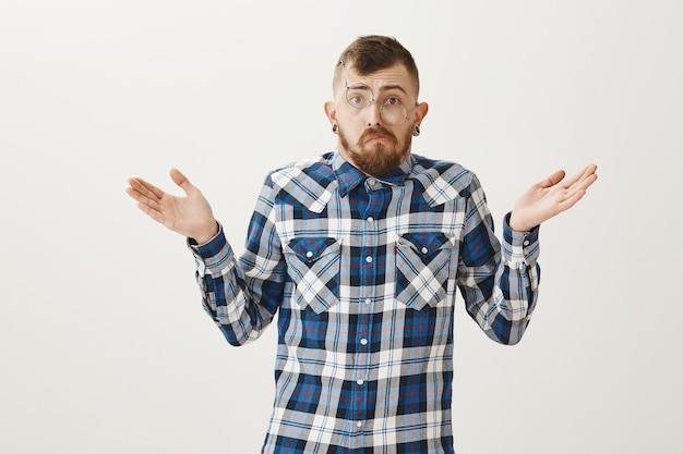 Głupi brodaty facet w przekrzywionych okularach wzrusza ramionami i wygląda na nieświadomego