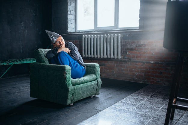 Głupi człowiek w kasku z folii aluminiowej, oglądający telewizję, ochrona umysłu, koncepcja paranoi. ufo, teoria spiskowa, fobia telepatyczna