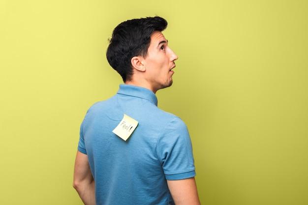 Głupi mężczyzna w niebieskiej koszulce polo z żółtą karteczką z głupcem na plecach głupio patrząc w górę