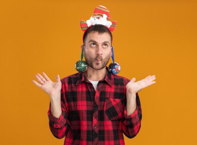 Głupi młody kaukaski mężczyzna ubrany w opaskę świętego mikołaja z zaciśniętymi ustami, pokazując puste ręce patrząc w górę z bombkami wiszącymi z jego uszu na pomarańczowym tle