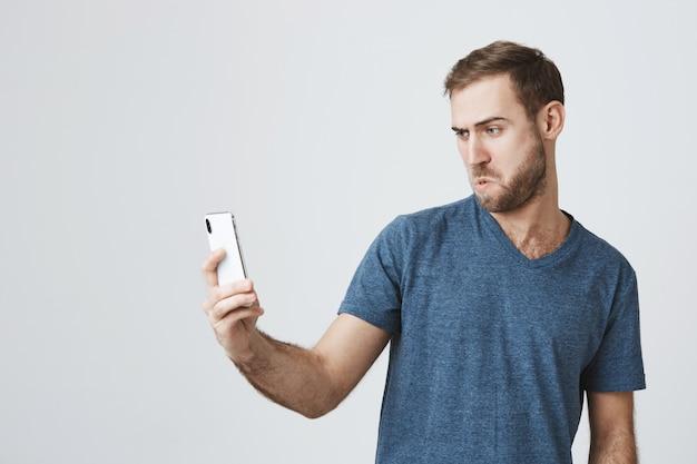 Głupi, przystojny facet, biorąc selfie na smartfonie, dąsając się