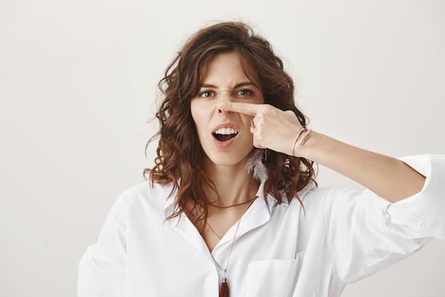 Głupia figlarna dziewczyna wygłupia się, pokazując grymasy