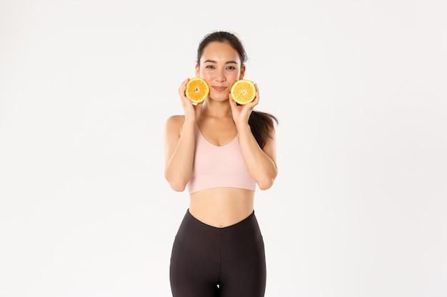 Głupia i urocza azjatycka dziewczyna fitness, lekkoatletka odchudzająca się podczas treningu, treningów na siłowni i zdrowej diety, pokazująca dwie połówki pomarańczy.