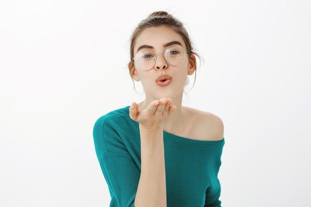 Głupia i urocza młoda kobieta dąsająca się, dmuchanie buziakiem