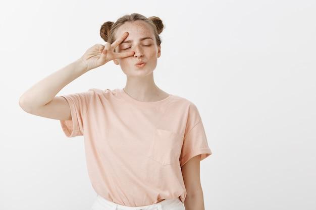 Głupia i urocza nastolatka pozuje na białej ścianie