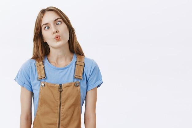Głupia i zabawna śliczna dziewczyna dąsająca się i mrużąca oczy, robiąc śmieszne miny