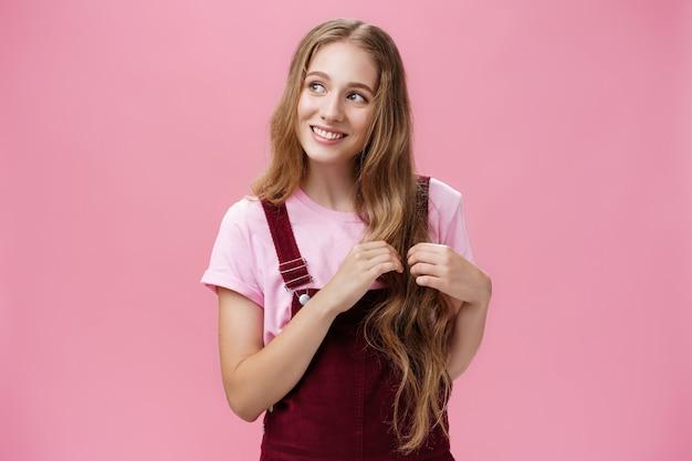 Głupia, miła i przyjazna, urocza dziewczyna marzy, zbierając kosmyki włosów i patrząc w lewo z ładnym, uroczym uśmiechem, wyobrażając sobie uroczą scenę pozującą zalotnie i szczęśliwie na różowym tle.