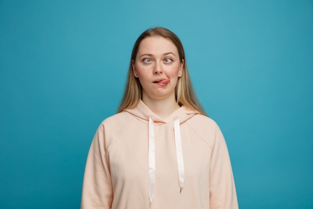 Głupia młoda blondynka pokazuje język ze skrzyżowanymi oczami